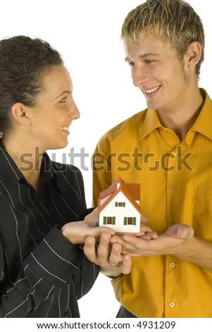 Young, happy couple holding house miniature. They're looking at each other. White background - stock photo