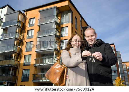 Young happy couple holding keys to their new home - stock photo
