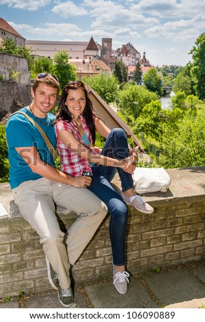 Young happy couple holiday portrait travel city sitting and smiling - stock photo