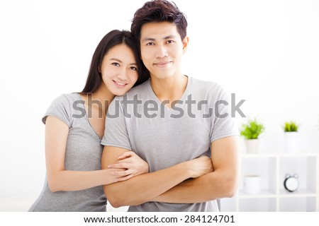 Young happy couple hugging and smiling - stock photo