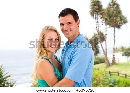 young happy couple hugging, background is sea view - stock photo