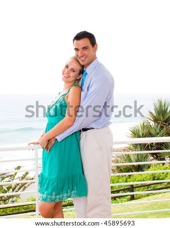young happy couple hugging on balcony, background is sea view - stock photo