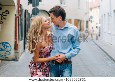 Young happy couple hugging while walking on the street. Smiling man and cheerful woman having fun in the city.