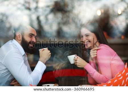 Young happy couple in a cafe, the view from the street through a window - stock photo