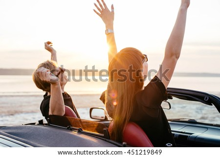 young happy couple in cabriolet in sunset light
