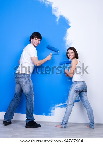 Young happy couple in casuals brushing the wall - rear view