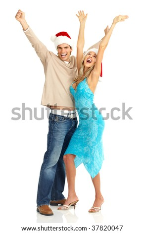 Young happy couple in Christmas hats. Isolated over white background - stock photo