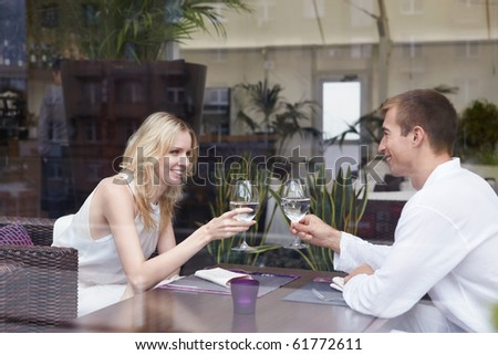 Young happy couple in love at a restaurant - stock photo