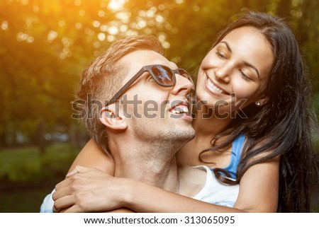 Young happy couple in love having a good time outdoors - stock photo