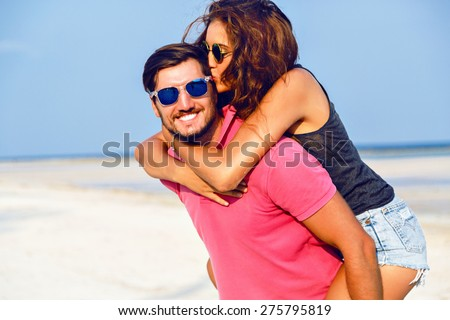 Young happy couple in love having fun and going crazy at the beach at nice sunny summer day, young woman jumping on her boyfriend, positive emotions. - stock photo