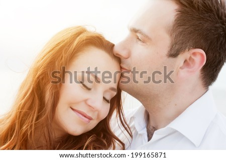 Young happy couple in love in a romantic moment of man kissing his wife in a forehead on the beach in summer sunshine.  - stock photo
