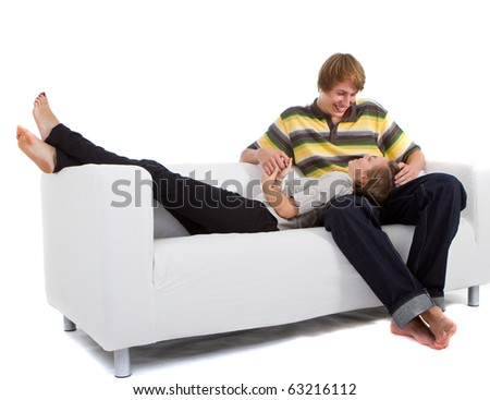 Young happy couple in love relaxing on a white couch enjoying their time together. - stock photo