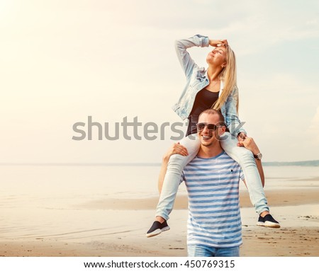 Young happy couple in love walking by the beach at summer sunset. Man Carrying girlfriend on Shoulders. Happy young family have a fun. Travel and vacation concept. - stock photo