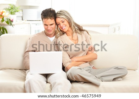 Young happy couple in love with laptop at home - stock photo