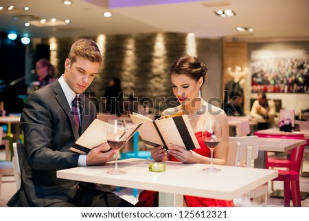 young happy couple in restaurant reading menu - stock photo