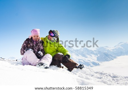 Young happy couple in snowy mountains. Winter sport vacation - stock photo