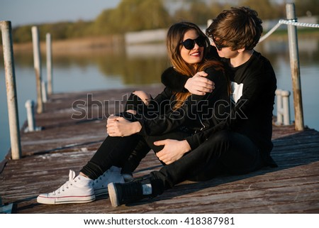 Young happy couple in sunglasses resting on a pier and embracing on a sunny summer day - stock photo