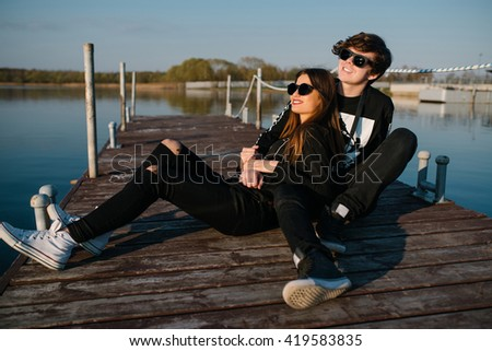 Young happy couple in sunglasses resting on a pier and embracing on a sunny summer day. love concept - stock photo