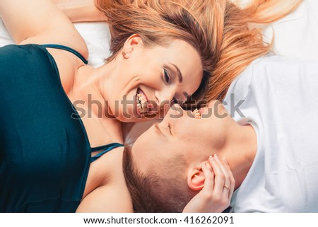 Young happy couple in the bedroom. They look at each other.