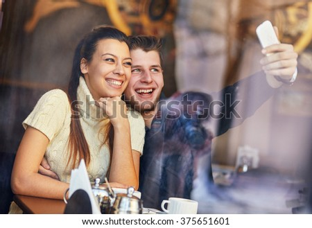 Young happy couple in the cafe, taking photo. - stock photo