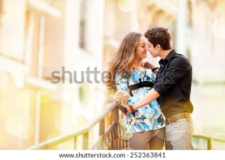 Young happy couple in the city. Young man and beautiful woman on street at dating. Kiss of two lovers in the city. Walking through the city day.  Love between two people. Honeymoon. Love story series - stock photo