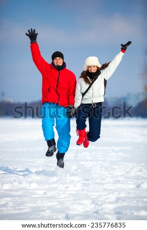 Young happy couple jumping outdoors. Cold winter season and snowfield. - stock photo