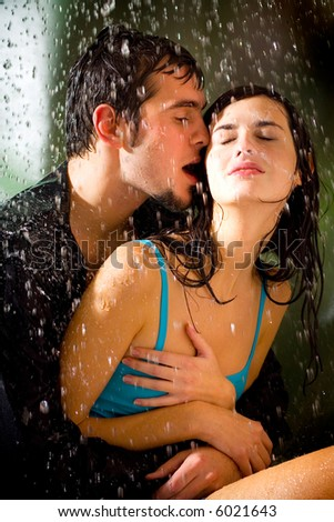 Young happy couple kissing and hugging under a rain - stock photo