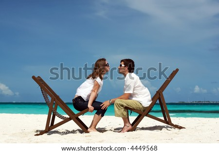 Young happy couple kissing at tropical white sand beach