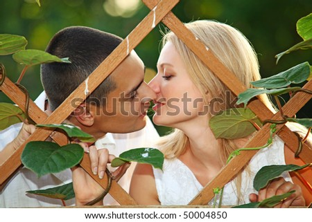 Young happy couple kissing at wooden lattice - stock photo