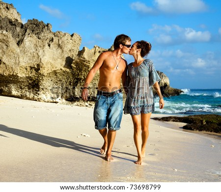 Young happy couple kissing during a walk along the coast - stock photo