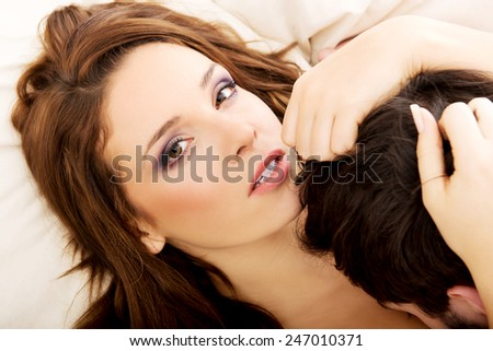 Young happy couple kissing on the bed. - stock photo