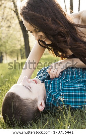 Young happy couple kissing on the grass.