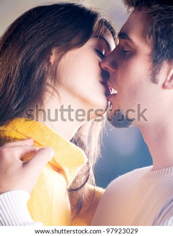 Young happy couple kissing outdoors - stock photo