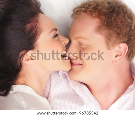 Young happy couple kissing over white background