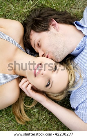 Young happy couple laying on grass - stock photo