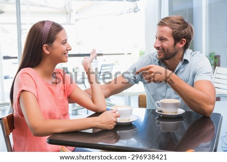 Young happy couple looking at each other inside a cafe - stock photo