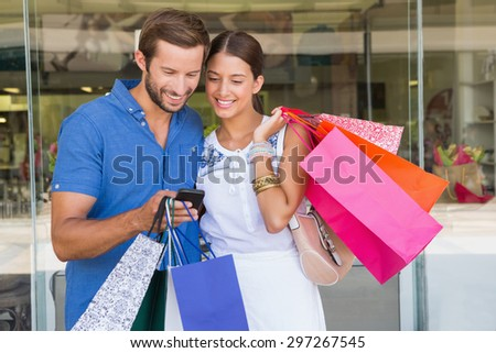 Young happy couple looking at mobile phone after shopping - stock photo