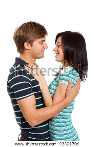 Young happy couple love smiling, looking to each other and hug, isolated over white background - stock photo