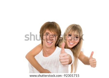 Young happy couple love smiling, wear white shirt, looking at camera show thumb up gesture point at you, isolated over white background - stock photo