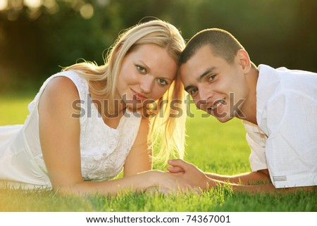 Young happy couple lying down on grass and holding hands - stock photo