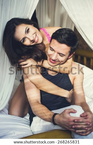 Young happy couple lying in bed in the sunny morning, smiling and having fun together
