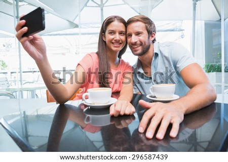 Young happy couple making a selfie in the cafe - stock photo