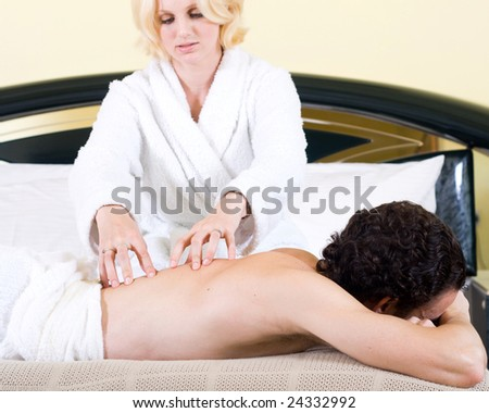 Young happy couple making massage in bedroom - stock photo