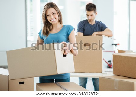 Young happy couple moving in their new house and unpacking boxes, she is carrying a carton box and smiling at camera - stock photo