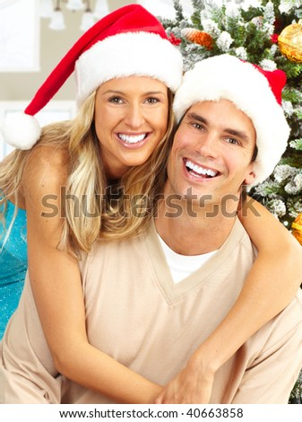 Young happy couple near  a Christmas tree at home - stock photo