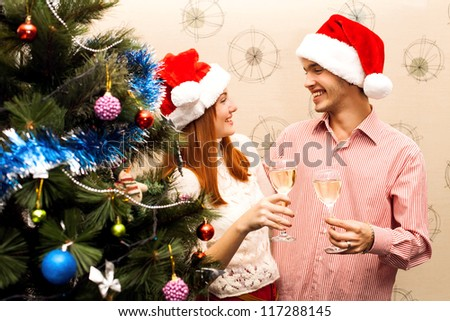 Young happy couple near a Christmas tree drinking champagne