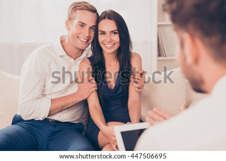 Young happy couple on reception for family psychologist - stock photo