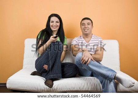 Young happy couple on sofa watching TV , they change channels and have fun - stock photo