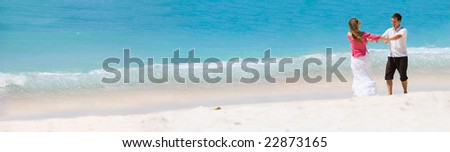 Young happy couple on white sand beach - stock photo