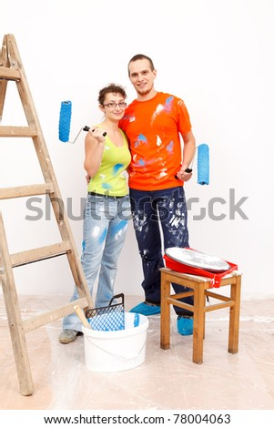 Young happy couple painting their new home interior together